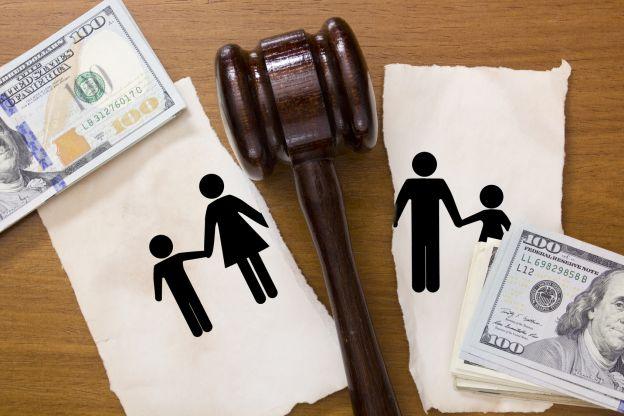Kartka z narysowaną rodziną przerwana na pół przez młotek sędziowski na każdej połówce znajdują się pieniądze