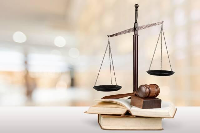 Waga szalkowa w obecności młotka sędziowskiego oraz książek