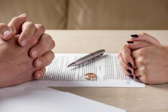 Mężczyzna i kobieta w obecności obrączek przy pozwie rozwodowym