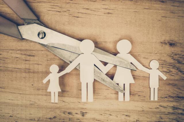 Tekturowa makieta przedstawiająca rodzinę która jest rozcinana na pół przez nożyczki